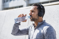 Man having a break from exercising wearing headphones and drinking from bottle - DIGF04057