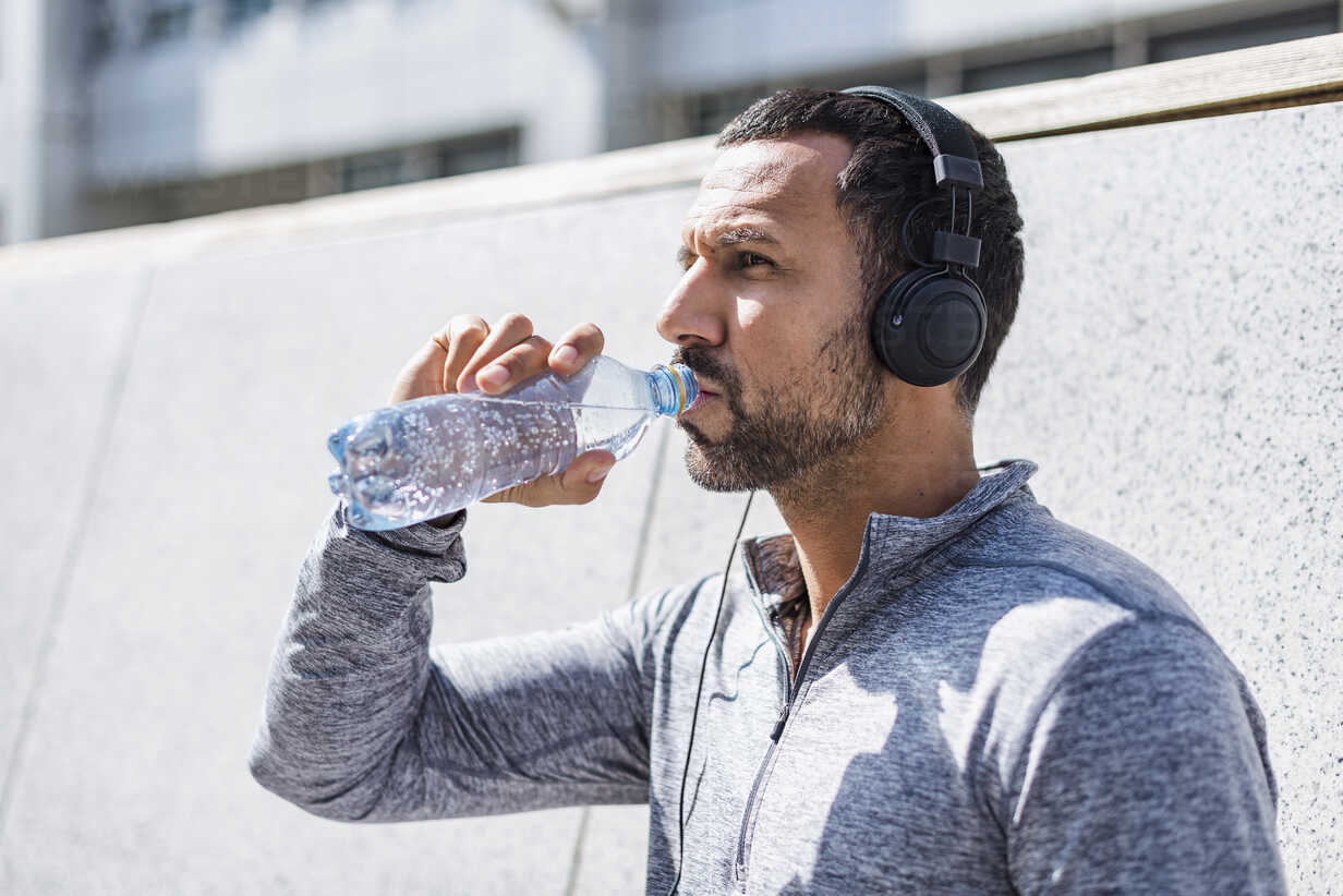 Man having a break from exercising wearing headphones and drinking from bottle - DIGF04057 - Daniel Ingold/Westend61