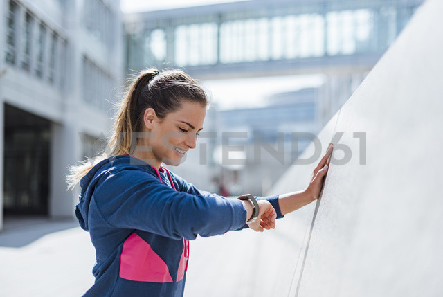 Smiling young woman having a break from exercising looking on smartwatch - DIGF04060