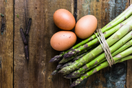 Green asparagus and brown eggs on wood - GIOF03922
