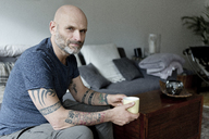 Tattooed man at home sitting on couch, drinking coffee - FLLF00018