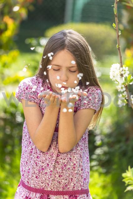 Portrait of girl blowing petals in garden - SARF03693