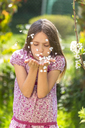 Portrait of girl blowing petals in garden - SARF03693