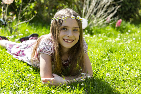 Portrait of happy girl lying on meadow in garden - SARF03696