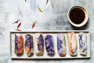 Vegan rice paper wraps (vietnamese summer rolls), filled with cabbage, carrots, bell pepper, rice noodles, and dipping sauce - SBDF03575