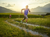 Athletes running on field path at sunset - CVF00331