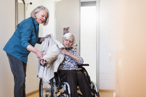 Woman taking care of old woman in wheelchair putting her jacket on - DIGF04069