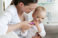 Mother brushing baby's teeth in bathroom - DIGF04075