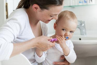 Mother brushing baby's teeth in bathroom - DIGF04075