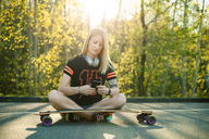 Blond woman with longboard sitting on street using smartphone - NAF00089