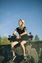 Blond woman with longboard sitting on wall at sunlight - NAF00092