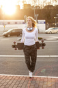Portrait of blond woman with headphones and longboard - NAF00095