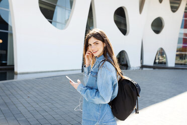 Spain, Barcelona, portrait of smiling young woman with backpack listening music with cell phone and earphones - VABF01553