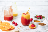 Strawberry and orange smoothie with curcuma and cinnamon on marble - RTBF01238