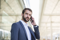 Young businessman on cell phone looking sideways - DIGF04086