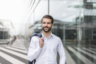 Portrait of smiling young businessman at glass facade - DIGF04101