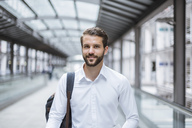 Portrait of smiling young businessman on moving walkway - DIGF04104