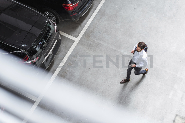 Young businessman with backpack on the go at parking garage - DIGF04110 - Daniel Ingold/Westend61