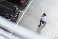 Young businessman with backpack on the go at parking garage - DIGF04110