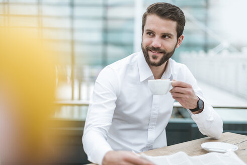 Smiling young businessman with newspaper and cup of coffee in a cafe - DIGF04113