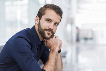 Portrait of confident young businessman sitting in waiting area - DIGF04125