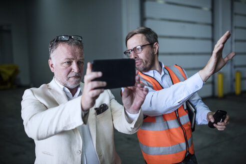 Man in reflective vest talking to businessman with cell phone in industrial hall - ZEF15405