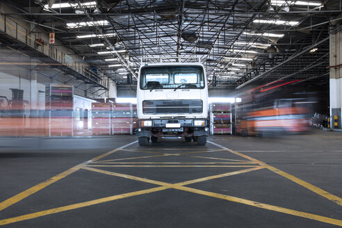 Parked truck in warehouse and moving forklifts - ZEF15420