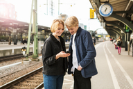Smiling teenage girl showing mobile phone to young man while standing on railroad station platform - MASF07102