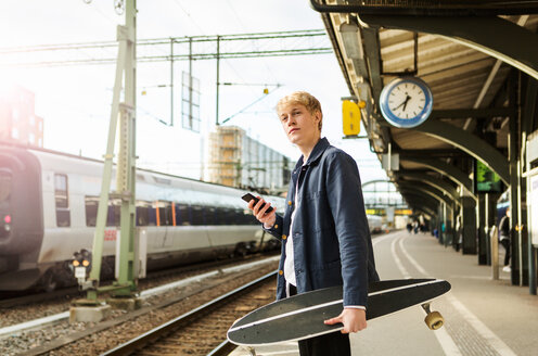Young man holding mobile phone and skateboard while waiting on railroad station platform - MASF07105