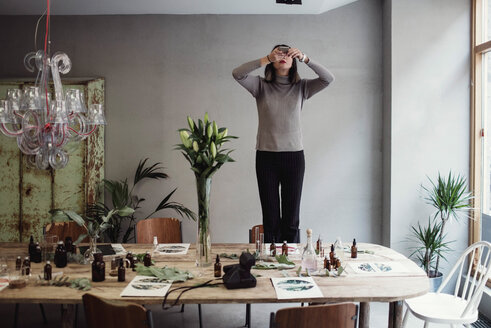 Young woman standing on chair photographing perfume bottles over table in workshop - MASF07189
