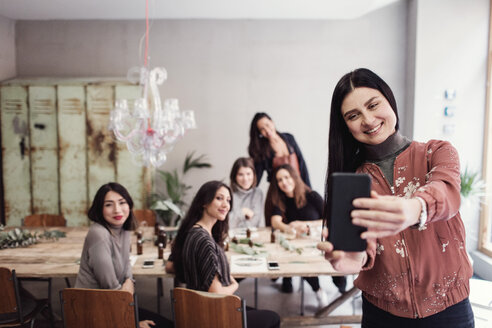 Smiling woman taking selfie with female colleagues at workshop - MASF07207