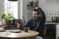 Man with headphones using mobile phone while sitting at table in kitchen - MASF07258