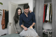 Smiling woman standing with man hanging clothes in coathanger by closet at bedroom - MASF07264