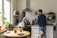 Smiling couple talking while working in kitchen at home - MASF07273