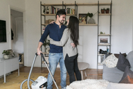 Man embracing woman while using vacuum cleaner in living room - MASF07276