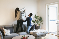 Couple adjusting painting on wall while leaning on sofa at home - MASF07282