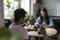 Man having coffee while woman using mobile phone at table in kitchen - MASF07288