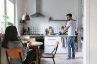Smiling man washing utensils while woman having drink at table in kitchen - MASF07291