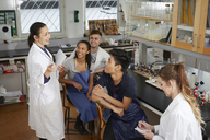 Happy mature teacher explaining to young multi-ethnic university students sitting in chemistry laboratory - MASF07321
