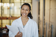 Portrait of smiling young chemistry student wearing lab coat standing with book in university - MASF07330