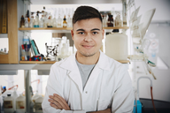 Portrait of smiling young male chemistry student standing with arms crossed in college laboratory - MASF07342