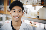 Portrait of confident young male university student standing at chemistry laboratory - MASF07345