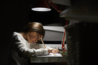 Girl studying while sitting at illuminated desk in darkroom - MASF07369