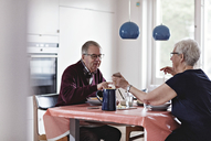 Full length of senior couple eating food at dining table - MASF07381