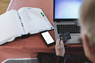 High angle view of retired senior man paying bills through credit card while using laptop at dining table - MASF07384