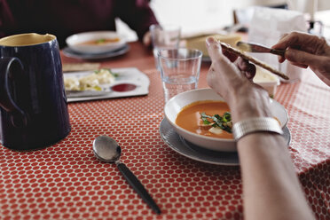 Cropped image of senior couple sitting with food at dining table - MASF07396