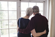 Rear view of retired couple looking through window at home - MASF07402