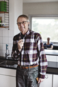 Portrait of smiling senior man talking on smart phone through in-ear headphones while standing in kitchen at home - MASF07405