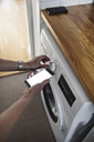 Cropped hands of senior woman holding mobile phone while using washing machine in bathroom at home - MASF07417