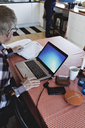 High angle view of retired senior man using laptop while sitting with financial bills at dining table - MASF07441